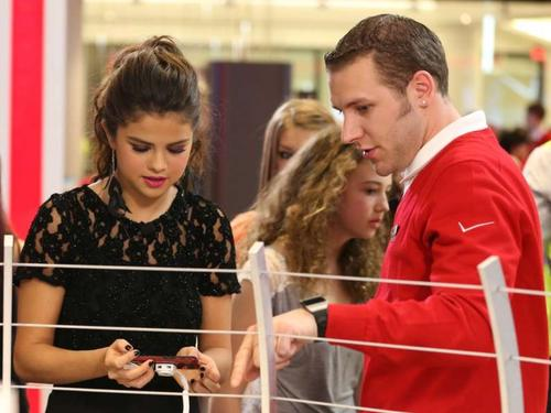 She's come such a long way since Barney & Friends: Selena Gomez fiddles with something in the Verizon Wireless store.