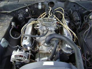 Engine compartment of 1973 Plymouth Scamp, with alternator clearly visible at left front  and the separate voltage regulator bolted to the side of the engine compartment.