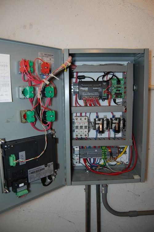 The control panel contains an AutomationDirect DirectLogic 05 Micro Brick PLC, a C-More HMI panel, I/O, and associated components.