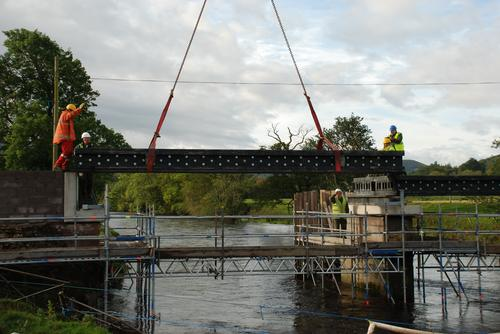 The crew lowers composite panels made from recycled plastics into place in the 90-foot Scottish bridge structure. Source: Axion International