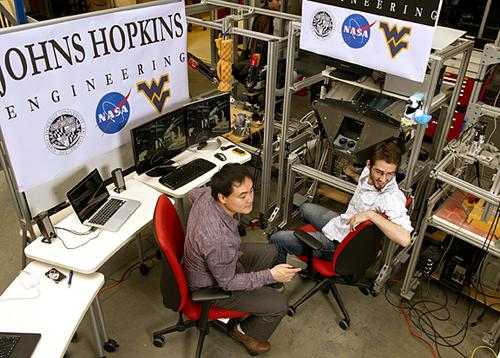 Johns Hopkins University graduate students Tian Xia, left, and Jonathan Bohren, right, use a modified Da Vinci medical robot console (behind Bohren) to control an industrial robot at NASA Goddard Space Flight Center 30 miles away. This demonstrates how medical robotics technology could help repair and refuel space satellites.   (Source: Will Kirk/Homewoodphoto.jhu.edu)