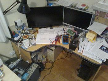 Nicholas Lee's second photo shows his desk with its PCs and a randomly strewn covering of schematics, test gear, oscilloscope, tools, and printed-circuit boards, as well as his trusty soldering iron.
