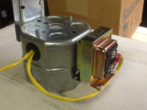 A low-voltage transformer attached to a four-inch octagonal electrical junction box.