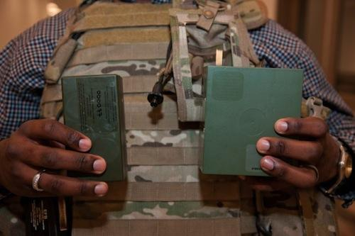 Christopher Hurley, an electronics engineer with the US Army Research, Development, and Engineering Command, holds a half-size BA-5590 battery, left, along with the standard version. The Army is researching the use of lighter battery materials to lighten the load for soldiers. (Source: Army)