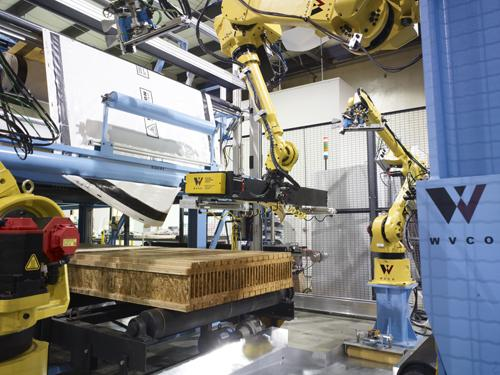 For wrapping operations where engineered wood made of particle board and laminated pieces has replaced solid beams used in the past, advanced robotics both improve safety and more precisely coordinate the manufacturing process.   (Source: PRE-TEC)