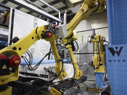 Concern for worker safety when climbing on the wood to stretch the wrapping led to development of the new robotic system. Robots now bring in each piece, accurately measure and stretch the wrapping to match the piece size, apply the sealant, and stack the wood for distribution.   (Source: PRE-TEC)