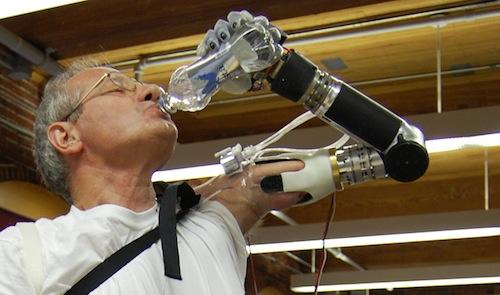An amputee uses a DEKA arm to drink from a bottle of water. The Defense Advanced Research Projects Agency and VA Research are working with DEKA Research to optimize the modular and motorized arm -- the most advanced arm prosthetic to date -- for commercial use. (Source: DEKA)