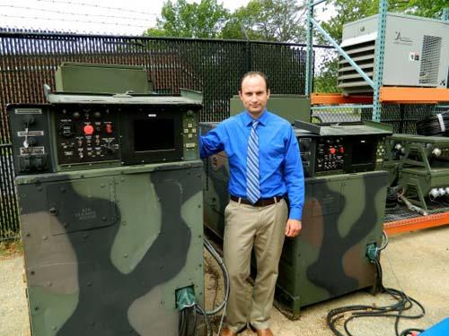 Christopher Wildmann, an electrical engineer with the US Army Research, Development and Engineering Command, stands between a 60 kW Tactical Quiet Generator, left, and a 30 kW unit that were modified to enable a microgrid.   (Source: US Army)