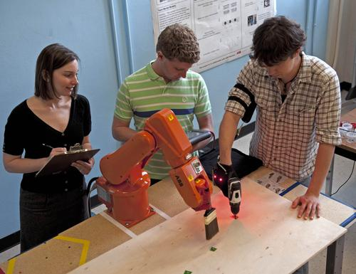 Professor Julie Shah with graduate students Ron Wilcox, center, and Matthew Gombolay coordinate human-robotic interaction while developing an algorithm that lets factory robots predict humans' movements. (Source: William Litant/MIT)