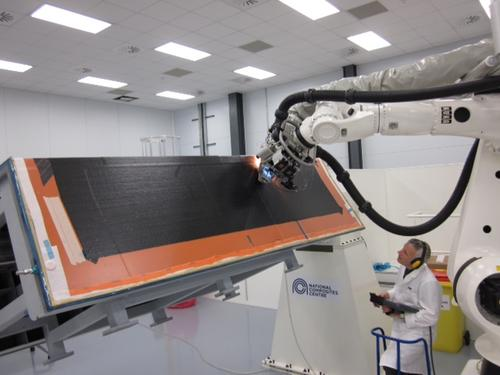 The first automated fiber placement machine in the UK, shown here with employee Tim Smith of GKN Aerospace, will help speed production of complex composite aircraft structures like wings.   (Source: National Composites Centre)