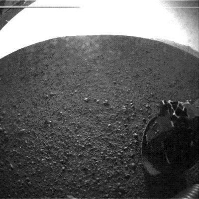 One of Curiosity's six wheels is shown in an early photo from the surface. The rim of Gale Crater is visible in the upper right.   (Source: JPL)