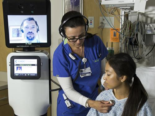 A nurse examines a patient under the watchful eye of a doctor via the RP-VITA, a robot co-developed by iRobot and InTouch Health that can autonomously travel around a hospital and allow a physician to administer care as if he or she is in the room with a patient.   (Source: InTouch Health)