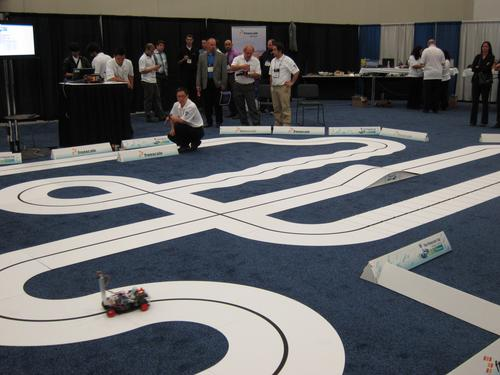 On the show floor, Freescale ran an autonomous vehicle competition called 'the Freescale Cup.' Model vehicles in the competition vied for fastest lap times by using onboard cameras to follow a line in the middle of the miniature roadway. The contest supplied vehicle chassis, rear-wheel drive motors, and powertrain controllers that incorporated Freescale's Qurivva microcontrollers. Competitors included GM, Ford, Chrysler, Continental, TRW, Bosch, Panasonic, Visteon, Aisin, and Johnson Controls.   (Source: Freescale Semiconductor)