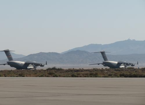 Two Air Force C-17 planes prepare to take off in tight formation as part of a test of vortex surfing. The technique is similar to bicycle racers or migrating birds forming tight groups to conserve energy. (Source: Air Force Research Lab)