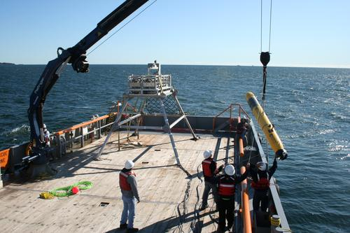 Researchers launch a Bluefin robotic vessel while a docking station for the vehicle sits on the deck of the ship. The docking station, developed by the Battelle Memorial Institute, will let unmanned vessels recharge their batteries and exchange data with researchers during missions at sea. (Source: Battelle Memorial Institute)