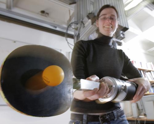 Researcher Katharina Muelling poses with a ping pong playing robot she and her team at the Technical University of Darmstadt in Germany designed and built. The robot is comprised of an arm to which a paddle is attached as well as a camera that watches the table and area of play, responding to the opponent's moves.   (Source: The Technical University of Darmstadt)