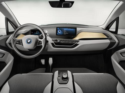 Above the steering column and behind the instrument cluster, a horizontally mounted wooden panel spans the full width of the interior. (Source: BMW)