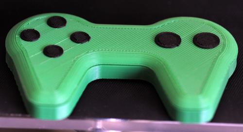 A conductive thermoplastic can be used with low-cost, hobbyist 3D printers to produce complete, customized electronic devices, such as this computer game controller.