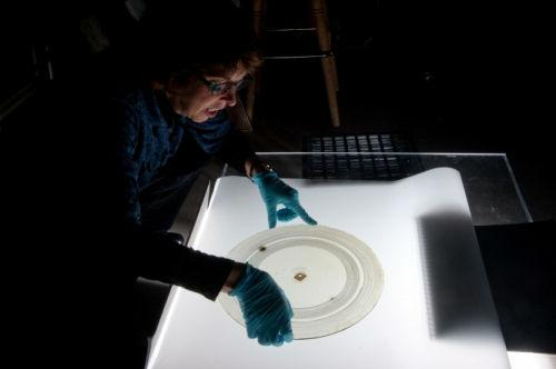 National Museum of American History curator Carlene Stephens examines a glass disc recording containing the audio of a male voice repeating 'Mary had a little lamb' twice, made more than 100 years ago in Alexander Graham Bell's Volta Lab.   (Source: Rich Strauss, Smithsonian)