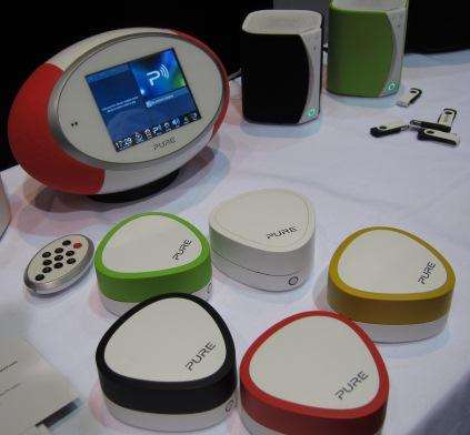 PURE, which initially built its reputation by developing Internet radio, has added wireless HiFi adapters to WiFi and Bluetooth (shown, front) along with wireless speakers. Plug in the HiFi adapter, and the company claims you can transform a HiFi system into a multi-room audio system. PURE also introduced portable wireless speakers (shown, rear) with WiFi and Bluetooth connectivity. The wireless speaker offers 360-degree sound (mono and stereo). WiFi can be used to stream synchronized audio to multiple wireless speakers in and outside the home.