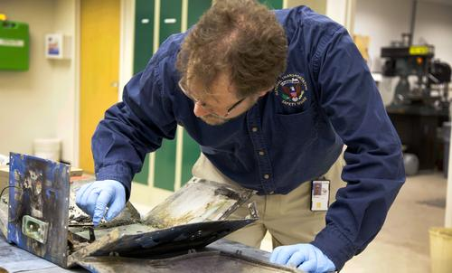 An NTSB engineer examines the casing from the battery involved in the JAL Boeing 787 flight in Boston.   (Source: NTSB)