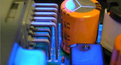 A silicone conformal coating has been spray-applied to automotive controllers, and fluoresces under UV light to aid visual inspection of the coating's coverage.   (Source: Dow Corning)