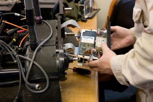 A technician works on a Foster-Miller robot.   (Source: Dave Bullock)