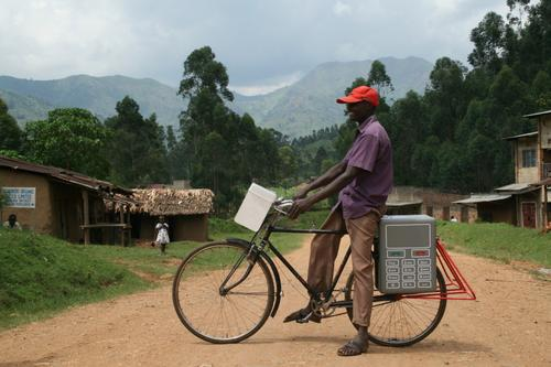 A man in Bududa Village, Uganda sits atop a bicycle on which is mounted a mobile charging unit developed by the BuffaloGrid Project that can charge a cellphone via text message.   (Source: The BuffaloGrid Project)