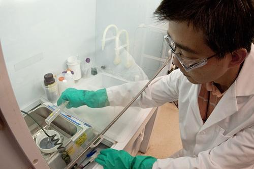 Hao-Chih Yaun, a researcher at the National Renewable Energy Laboratory, pours a mixture of hydrofluoric acid and hydrogen peroxide onto a silicon wafer as part of the process to create a dark solar cell.   (Source: Dennis Schroeder/NREL)