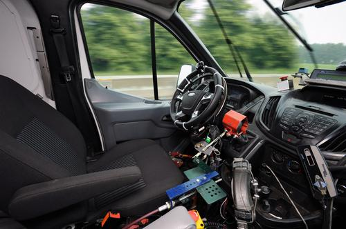 Ford's robotic driving system includes a ring gear attached to the steering wheel, a shifter actuator(in red), and an accelerator actuator (next to the driver's seat).(Source: Ford)