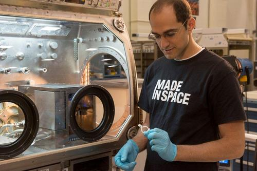 Made in Space deputy program manager Matthew Napoli examines a piece printed by the engineering test unit 3D printer, shown inside the Marshall Space Flight Center's Microgravity Science Glovebox. (Source: Marshall Space Flight Center)