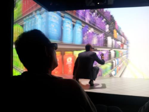 Dassault Systemes' virtual reality cave technology in use at the SolidWorks 2014 release event. A user is ducking down to see the bottom of a virtual product shelf.