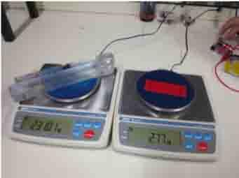 The Perspex blocks lifted by the artificial muscle weigh 231 gm (left), more than 80 times the weight of the electroactivated polymer (EAP) muscle (right) at 2.77 gm.   (Source: National University of Singapore)