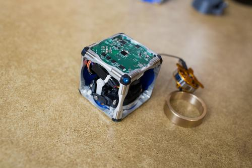 MIT researchers have developed self-assembling, flywheel-driven modular cube robots, shown here with innards exposed and flywheel pulled out. (Source: M. Scott Brauer/MIT)