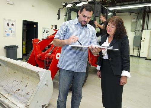 Purdue University professor Monika Ivantysynova and doctoral student Naseem Daher discuss research related to new hydraulic steering technology, while graduate student Michael Sprengel looks over the electronic controls of a front loader. Researchers led by Ivantysynova, a fluid systems professor at Purdue's School of Mechanical Engineering, have shown how to reduce fuel consumption while improving the efficiencyof hydraulic steering systems in heavy construction equipment.(Source: Mark Simons/Purdue University)