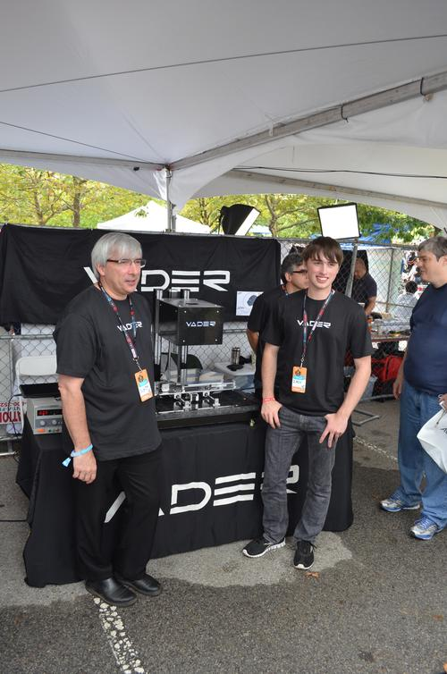Scott Vader (left), chief engineer of Vader Systems, and president Zachary Vader (right) show off their prototype 3D printer for making solid metal, full-production parts, at the 2013 New York Maker Faire. Both are mechanical engineers. (Source: Vader Systems)