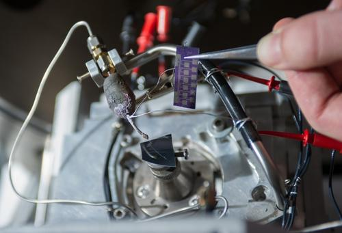 A heated capillary micro-nozzle is installed on the deposition stage of a focused electron beam induced deposition (FEBID) system, along with the test chip used for electrical characterization of deposits for graphene interconnects.   (Source: Rob Felt, Georgia Tech)