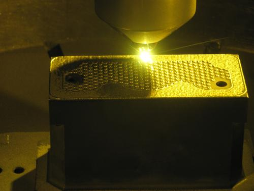 Two second-round America Makes projects led by Optomec involve its LENS process, based on metal laser deposition. Shown here, the LENS 3D printer builds a metal tool with internal cooling cavities used in the production of refrigerator parts.(Source: Balmar d.o.o.)