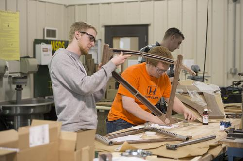 Senior engineering students Jake Miller, David Yoder, and Gerrit Start work on wooden bike frames for their capstone team project at Cedarville University.   (Source: Scott Huck)