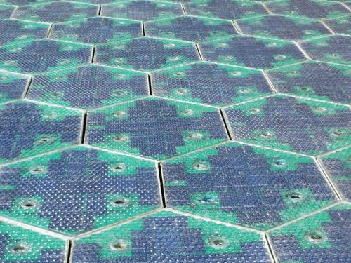 Shown is an array of solar panels paving a roadway -- the invention of Solar Roadways -- a project that aims to create parking lots and roads of specially designed solar arrays that have been built for durability.   (Source: Solar Roadways)