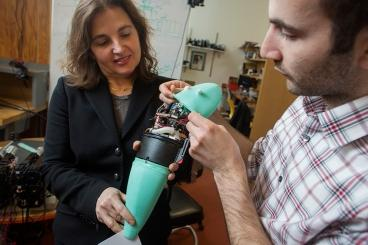 Andrew Marchese, doctoral candidate in EECS at MIT (right), and Dr. Daniela Rus, professor in EECS and Director of CSAIL, hold a soft robotic fish developed at CSAIL by Marchese. The fish can move as quickly and nimbly as a real fish and represents a new direction in soft robotics.   (Source: Computer Science and Artificial Intelligence Laboratory/MIT)