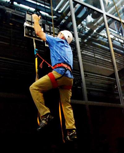 During testing, an operator climbed 25 feet vertically on a glass surface using no climbing equipment except a pair of handheld paddles covered with a polymer microstructure adhesive material. The climber wore, but did not require, a safety belay.  (Source: DARPA)
