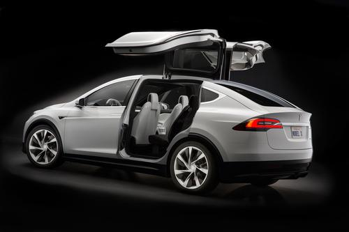 The Model X crossover will hit the road two years before the newly announced Model 3. It will use 'Falcon wing' doors that open upward, but not outward. The design will let adults walk into the vehicle instead of crawling in.(Source: Tesla Motors)