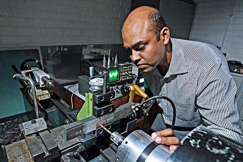 Loughborough University researchers have come up with a method for machining aerospace-grade, carbon fiber-reinforced composites using an ultrasonically assisted machining device. Team memberAnish Roy uses the device to drill composites.(Source: Loughborough University)