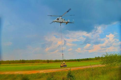 Lockheed Martin has completed a fully autonomous mission demonstration with two completely autonomous robotic vehicles performing resupply, reconnaissance, surveillance, and target acquisition. Shown here, a Lockheed Martin K-MAX unmanned helicopter delivers a Squad Mission Support System (SMSS) unmanned ground vehicle to a simulated battlefield. There the SMSS, equipped with a Gyrocam optical sensor for surveillance, will complete the resupply and then scan the 'hostile' area for enemy forces, transmitting images to a remote operator.   (Source: Lockheed Martin)