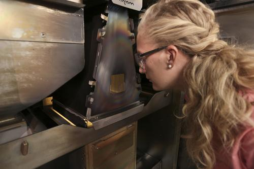 Caitlin Oswald, design and applied technology manager at Pratt & Whitney, inspects a part being made using additive manufacturing at the Pratt & Whitney Additive Manufacturing Center at the University of Connecticut.