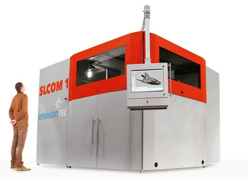 EnvisionTEC introduced what it says is the first industrial-scale 3D printer for producing woven fiber composite parts. The SLCOM 1 uses a process the company calls Selective Lamination Composite Object Manufacturing, which allows building composite parts using layer-by-layer laminated thermoplastic composite fabric sheets from a roll. Build volume of this first printer is 24inch  x 30 inch x 24 inch. It can process a wide range of custom-made thermoplastic reinforced unidirectional or multidirectional woven fibers. Composite matrix materials include woven glass fiber, woven carbon fiber, or woven aramid fibers reinforced with a choice of nylon 6, nylon 11, nylon 12, PEEK, PEKK, and polycarbonate. Composites can be tailored for toughness, environmental resistance, vibration dampening, low flammability, high wear resistance, and high strength-to-weight ratio.    (Source: EnvisionTEC)