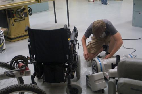 Tim Balz works on repairing a wheelchair. Source: FreedomChairs.org