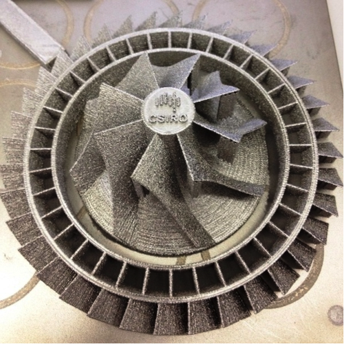 The compressor and blisk (blades plus disk) pictured in this image were made separately within the same build. According to CSIRO, this 3D printed titanium matched set reduces piece count (many fasteners), weight, labor, supply chain management, and cost. More titanium 3D printed pieces here.  (Source: CSIRO)