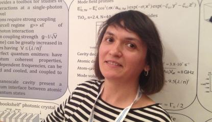 Elena Kuznetsova, an RQC scientist, stands before a poster paper outlining a new technique for transferring quantum information encoded on single photons to atoms, where they can be processed in a quantum computer.